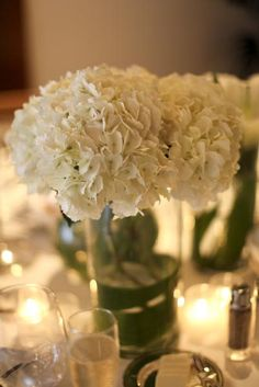This is perfect. Simple one kind of flower = centerpiece + votive candles. hydrangea centerpieces | white-hydrangea-centerpieces
