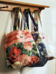 Easy Floral Tote What you'll need:    3/4 yard of fabric for bag and handles 1/4 yard of contrasting fabric for bag 5/8 yard of fabric for lining Thread to coordinate with fabrics 3-inch doily for applique motif Two buttons for trim