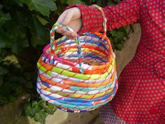 To make a recycled plastic bag basket you will need scissors, a bodkin or large tapestry needle, plenty of clear tape, around forty carrier bags (depending on the size of the basket) and garden twine.
