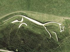 The Uffington White Horse is etched in chalk in A hillside in Oxfordshire, England.