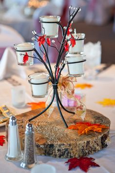 Really like the Rustic Idea for a fall wedding!!! Candle Centerpieces    A modern candle centerpiece balances on a rustic tree trunk slice adorned with red, orange, and yellow leaves. (Cute idea)