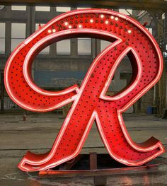 """Famous Rainier 'R' to make return atop Seattle brewery building. Pabst plans to re-light the sign at a free public party on October 24. """"The party will be a chance to celebrate the history of Rainier in Seattle and see the restored, glowing icon back in its rightful place atop the old brewery after a 13 year absence,"""" said McHugh."""