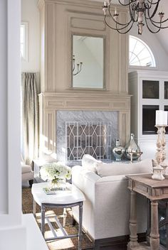 This living room is anchored by an antique mirror integrated into the overmantle of the fireplace.