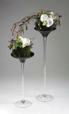 hoog glas en mosbol met orchidee en berkentak