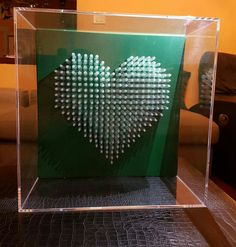 Green with envy is from the Love is the Drug heart sculpture series. 42 x 42 cm. Syringe on marine board inside plexiglass.  #syringes #art #artists #contemporary art #mixed media #contemporary wall sculpture