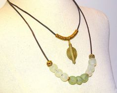 Pale green African beads and African brass beads are strung on leather for this unique doublse strand necklace. This would definitely add interest to