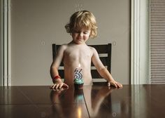 Shirtless boy looking at birthday cupcake while standing by wooden table