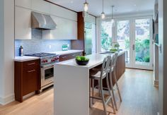 narrow kitchen with island and walnut cabinets. Beauparlant Design