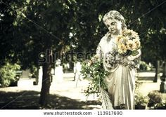 Statue of child, holding a bundle of flowers in a cemetery in Bratislava, Slovakia