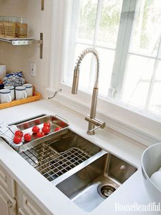"""Stainless-Steel Sink by sleek Franke Kubus sink """"You can drain dishes on the grid or wash lettuce and it's not sitting in a puddle of water. The coriander slots right into the sink. The 20-inch faucet has a pull-down spout and only requires one hole, which looks cleaner,"""""""