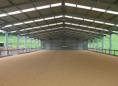 66ftX130ft indoor arena with a glass walls for natural lighting and an outdoor ring to the left of it