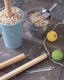 Make a place to hang string lights with poles stuck into gravel-filled flower buckets.