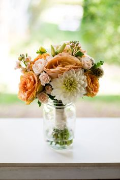 mason jar with orange pale pink and white floral arrangement #weddingflorals #tabledecor #weddingchicks http://www.weddingchicks.com/2014/02/06/rhythm-and-recovery-wedding/