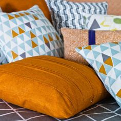 Spira Jaffa Light Turquoise Cushion from Hus & Hem teamed with a gorgeous coordinating burnt orange plain.   Spira's Jaffa cushion has a retro feel thanks to its triangular design and simple colour palette of turquoise, grey and orange.  The crisp graphic design looks fabulous when teamed with Spira's other patterns.