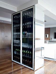 A varanda gourmet se uniu à sala de jantar para ampliar a área de degustação de vinhos. Ao ser demolida a parede entre os ambientes, restou a coluna estrutural. O arquiteto Diego Revollo solucionou a questão criando um móvel que envolve todo o pilar