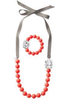 Parure Collier Color Crush Perles en acrylique couleur corail ornées d'une broche en forme de fleur pour sublimer le ruban gris. À assortir au bracelet de perles corail. Collier : Longueur de 109 cm avec fermoir ruban. Bracelet: 4,4 cm de diamètre avec système de réglage. Sans Nickel. Peut contenir des traces de plomb conformes aux normes européennes.