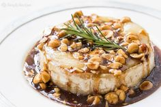 Festive Baked Brie! Drizzled with a sweet and sour honey sauce and toasted hazelnuts. Absolutely delicious with apple slices. On SimplyRecipes.com
