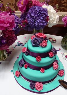 My actual wedding cake. Bright turquoise/ jade 3 tired wedding cake with purple ribbon and purple and pink sugarpaste flowers.