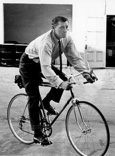 Robert Mitchum rides a bike on the studio lot, c. 1962.