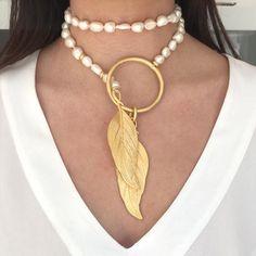 Collar largo y abierto de perlas de rio irregulares rematado con un aro y dos hojas laminadas en los extremos todo bañado en oro mate. Por encargo puede realiza