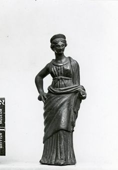 Greek bronze figure of a standing woman, perhaps Aphrodite, with one hand on hip, wearing chiton and himation and diadem.