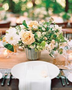 For these wild-looking vintage centerpieces, Kate Holt of Flower Wild arranged garden roses, popcorn viburnum, clematis vine, and hawthorne and olive greens in cement vessels.