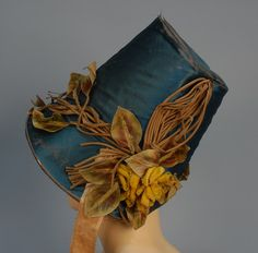 Teal silk satin poke bonnet with appliquéd cloth leaves, vines, and flowers, and yellow moiré ribbon ties, c. 1840s.