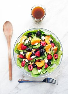 A large glass bowl of Berry Orange Spinach Salad with a small jar of Citrus Balsamic Vinaigrette, wooden spoon, and fork around it.