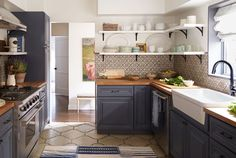 Kitchen with subdued blue cabinets, butcher-block countertops and a Spanish tile backsplash.