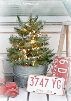 """Once upon a time I used to love a BIG tree dressed to the nines. But recently my taste has changed and now I adore smaller, simplier, more rustic and old fashioned. This little tree is just about perfect setting in it's galvanized mop bucket trimmed with red checked ribbon and twinkle lights. via The Cozy Old """"Farmhouse"""""""