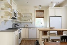 Fabulous traditional kitchen butcher block countertops features shaker style and schoolhouse pendant with white appliances and white kitchen, tile kitchen backsplash. Kitchen subway tiles features pendant lighting with kitchen shelves, wood flooring. Cream Kitchen Cabinets, White Kitchen Appliances, Kitchen Cabinet Design, Kitchen Shelves, Corner Shelves, White Cabinets, Open Cabinets, Kitchen Storage, Kitchen White