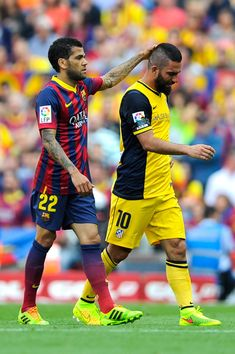 Dani Alves of FC Barcelona comforts Arda Turan of Atletico de Madrid as he leaves the pitch injured during the La Liga match between FC Barcelona and Club Atletico de Madrid at Camp Nou on May 17, 2014 in Barcelona, Catalonia.