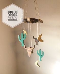 How perfect would this be for a boho, western, woodland, or rustic nursery? Handmade wood from scratch - it is complete with two cactus painted in a custom mixed paint color - Forest Mint, two buffalo skulls stained in Deep Honey, and four accent arrows stained in Natural Pine. #baby #mobile #genderneutral #wooden #boys #girls #southwestern #cactus #buffalo #arrows #nursery #unique #boho #western #diy