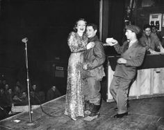 Marlene Dietrich In Germany. Actress Marlene Dietrich, 40, clad in slinky sequined evening gown, playfully making love to a blushing GI as comedian Freddie Lightner stands by on stage during her USO show for an audience of US servicemen in theater at the front. Location: Germany; Date taken: Feb. 27, 1945; Photographer: George Silk. USO Camp Shows, Inc. - ETO.   LIFE Photo Archive hosted by Google