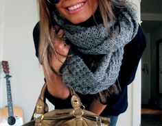 grey wool scarf, dark blue jacket, tanned, leather bag...
