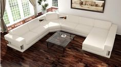 Deluxe Living Room Idea with Wooden Flooring and U Shaped White Leather Sofa Design near Glass Top Coffee Table also White Wall Paint Color and Wall Mounted Arts and Brown Curtains