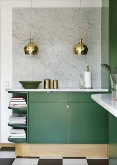 Kitchen with green cabinents and gold pendant lights.
