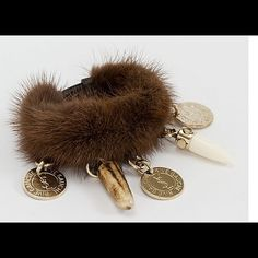 """Ysl mink charm cuff bracelet Yves Saint Laurent brown mink fur cuff with leather interior strap. Detailed with resin tooth charms and gold plated metal coins with signature YSL stamp. Adjustable interior buckle. Comes in velvet pouch. Made in France . Minor wear, great condition! 9.5"""" x 3.5"""" Yves Saint Laurent Jewelry Bracelets"""