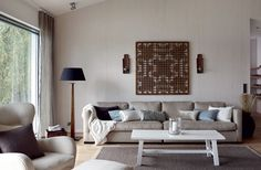 Olohuoneen selkeä-linjainen sohva on Bloomerista. Puinen taide-teos seinällä on vanha kiinalainen ikkunaritilä, joka ostettiin Classic & Chinese Furniture -liikkeestä Helsingintien varresta. Valkoinen sohvapöytä on puuseppätyttären tekemä. Olohuoneen ja ruokatilan verhot ja matto teetettiin Sisustusnallessa.