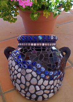 Mosaic terracotta pot with river rock, stained glass, travertine tiles, and glass gems Great for reglued broken pots Mosaic Planters, Mosaic Vase, Mosaic Flower Pots, Mosaic Tiles, Mosaics, Pebble Mosaic, Tiling, Mosaic Crafts, Mosaic Projects