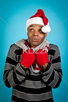 young man wearing santa hat and contemplating. - Young man wearing santa hat and contemplating over turquoise background, Model: Eddie Reid