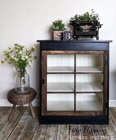 """This is a custom made cabinet featuring an old salvaged window. The interior has been painted with General Finishes Antique White Milk Paint. The exterior is painted with General Finishes Lamp Black Milk Paint, lightly distressed and sealed with Antique Wax."" - Fine Flipping"