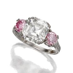 DIAMOND RING. The square emerald-cut diamond weighing 5.02 carats, flanked by round diamonds of pink hue weighing approximately 1.00 carat, mounted in platinum
