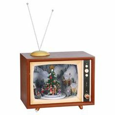 """Vintage television-shaped music box with a Christmas theme.  Product: Music boxConstruction Material: Plastic and resinColor: MultiFeatures: Festive addition to any holiday decorDimensions: 15.5"""" H x 6"""" W x 10"""" D Cleaning and Care: Dust with dry cloth"""