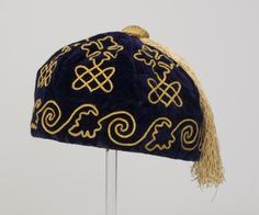 1880 Smoking Cap  Although soberly dressed in dark colours when outside the home, middle class men in the 1800s and early 1900s often favoured brightly coloured smoking jackets and caps when relaxing at home in the evening. This smoking cap is typical, with its luxurious materials and design of leaves and four-leaf clovers worked in gold braid.