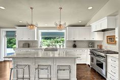 White shaker kitchen cabinets paired with marble countertops and glossy white beveled subway tile kitchen backsplash.