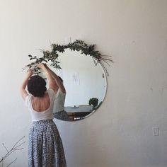 Foliage framed circular mirror