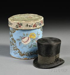 "Miniature Hatbox with a Gentleman's Top Hat, America, late 19th century, the round blue covered box with printed gilt and polychrome floral and horse decoration, the interior containing a black beaver top hat with a label for ""Dunlap & Co., New York"" firm, ht. 4 7/8, 2 7/8 in."