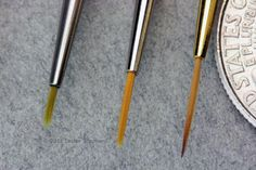 7  Mistakes to Avoid When You Paint Miniatures or Models: Two fine liner brushes on the right, a 3/0 and a 18/0 from different companies, with a shorter 'spotter' paintbrush on the left for comparison. The coin edge is from a quarter for scale.