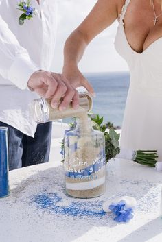 Sand ceremony in #Mykonos, Greece  The flowing sand and blending of the colors in the sand ceremony symbolize the bringing together of two lives into one. The two sands symbolize everything that the bride and groom have been or will become in the future. #weddinginmykonos #weddingingreece #sandceremony #mykonoswedding #weddingplannergreece